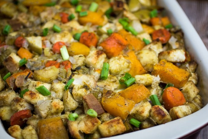 A casserole dish of stuffing with sweet potatoes, carrots and green onions.