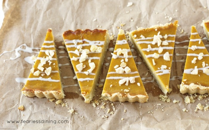 Wedges of butternut squash tart topped with glaze and toasted nuts on a piece of parchment paper.