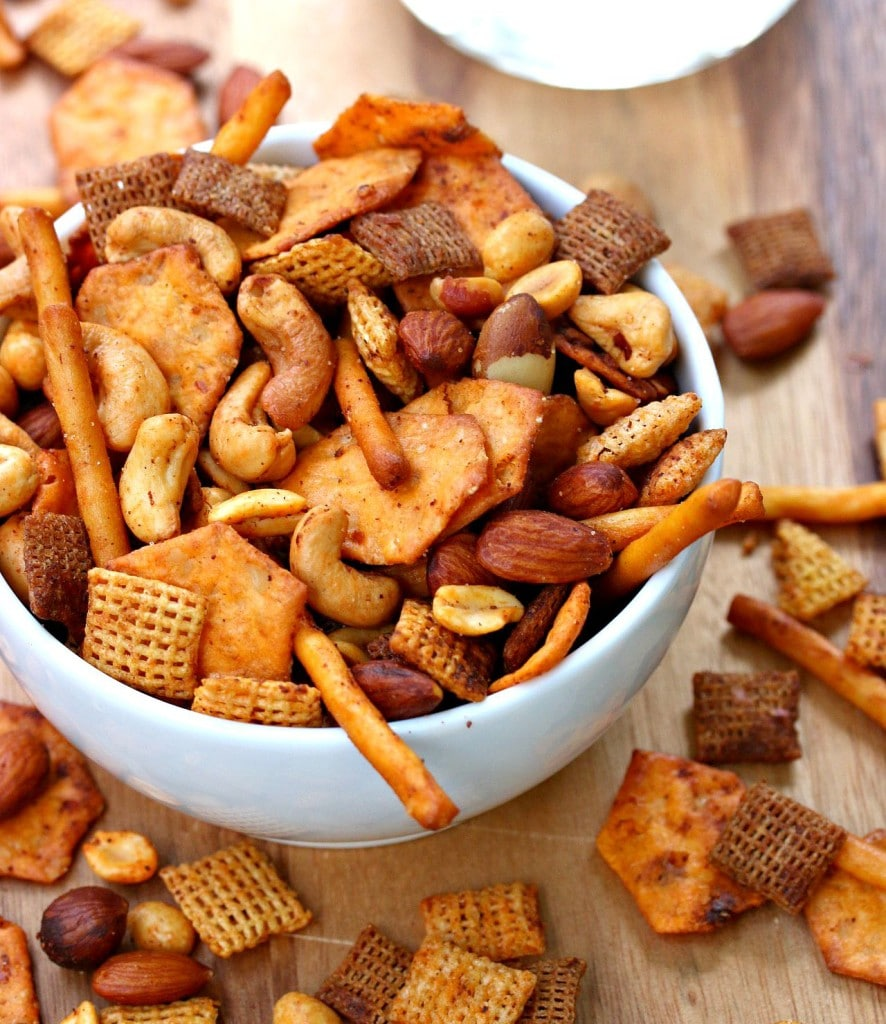A bowl of spiced chex party mix with pretzels.