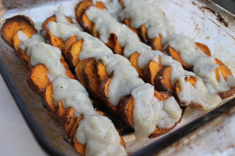 A platter of sweet potato rounds topped with creamy gravy.