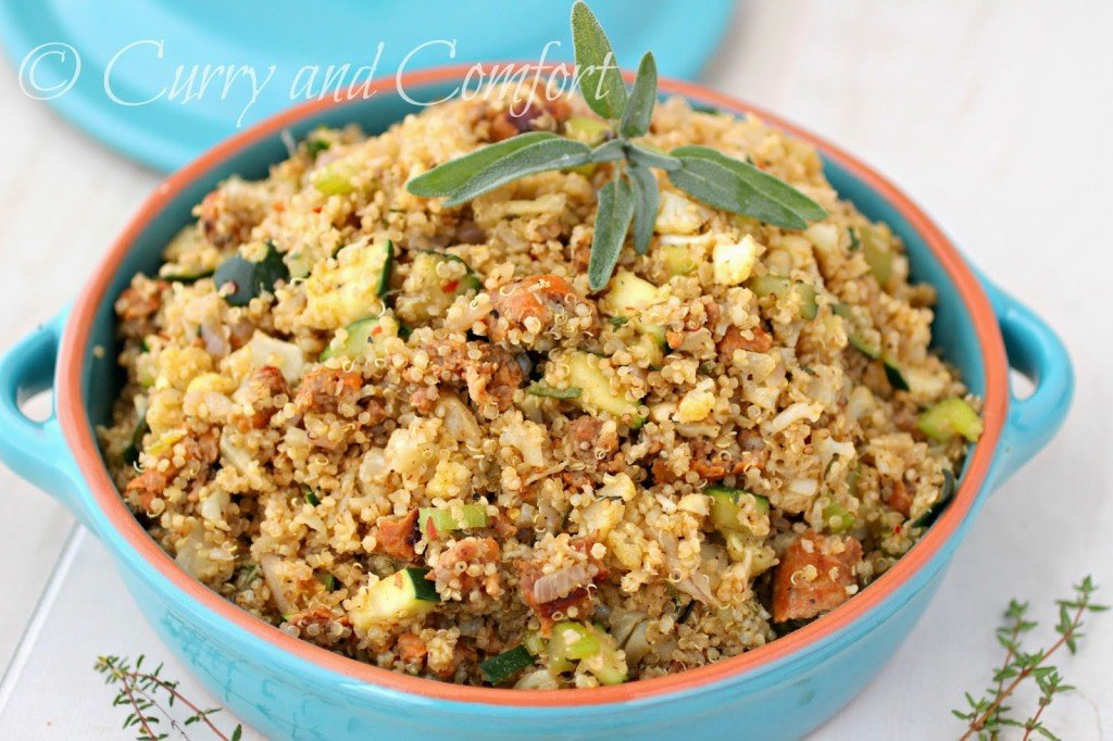 A casserole dish of quinoa and sausage stuffing topped with celery and thyme.