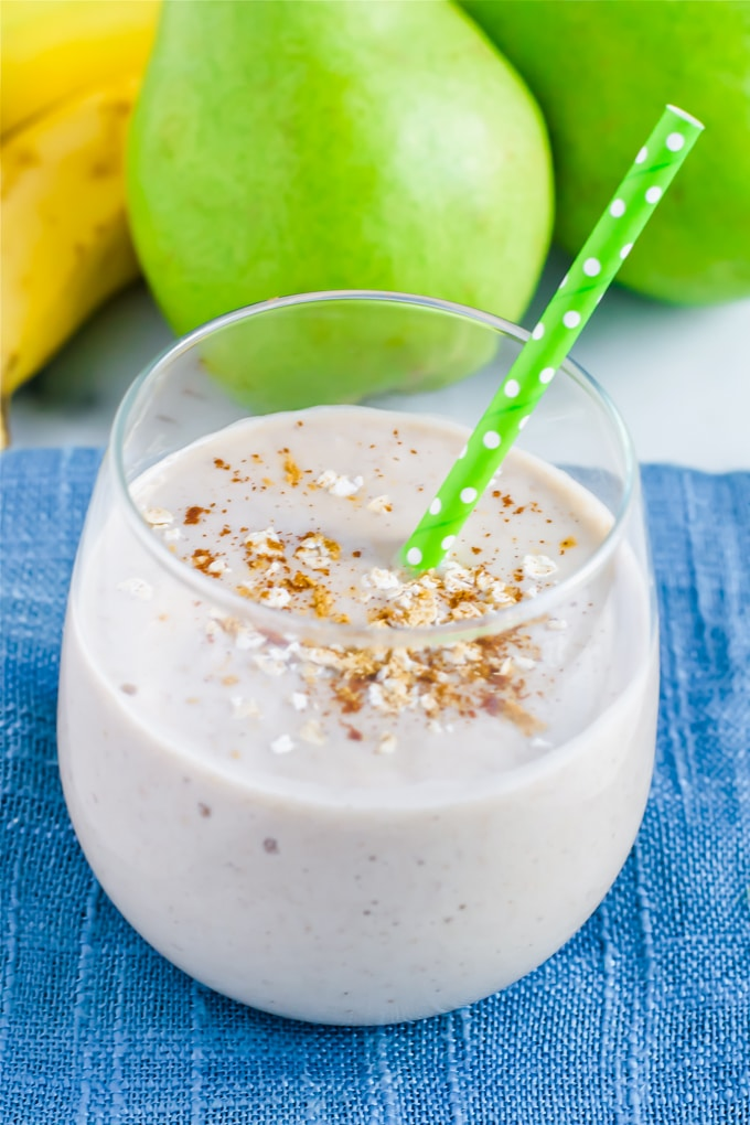 A glass with a ginger peat oatmeal smoothie with a green polka dot straw in it and pears in the background.