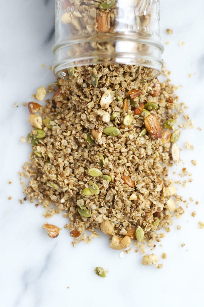 A mason jar of granola with almonds and pumpkin seeds spilling out of it.