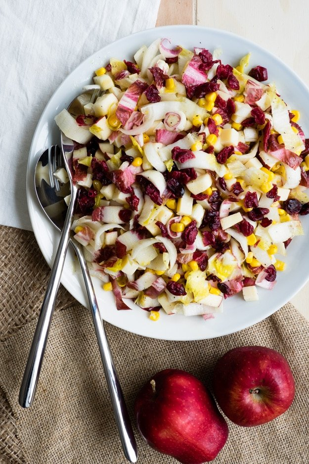 A bowl of apple and red cabbage salad with dried cranberries and corn on top.