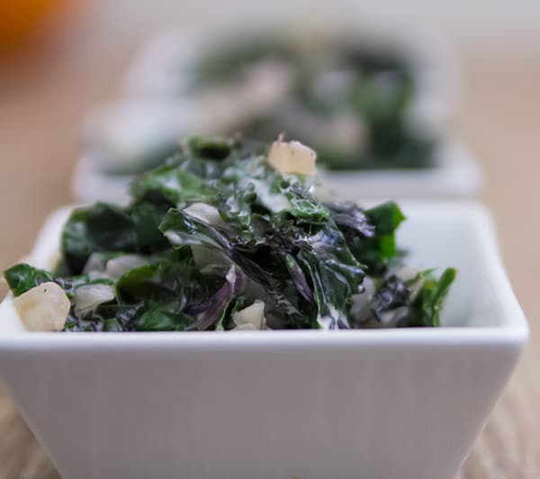 A bowl of creamy kale topped with sliced almonds.