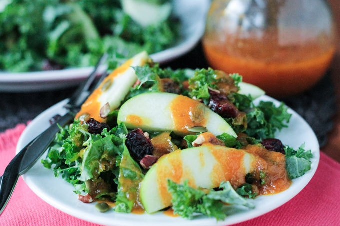A kale salad topped with dried fruits, granny sith apples and an orange dressing.