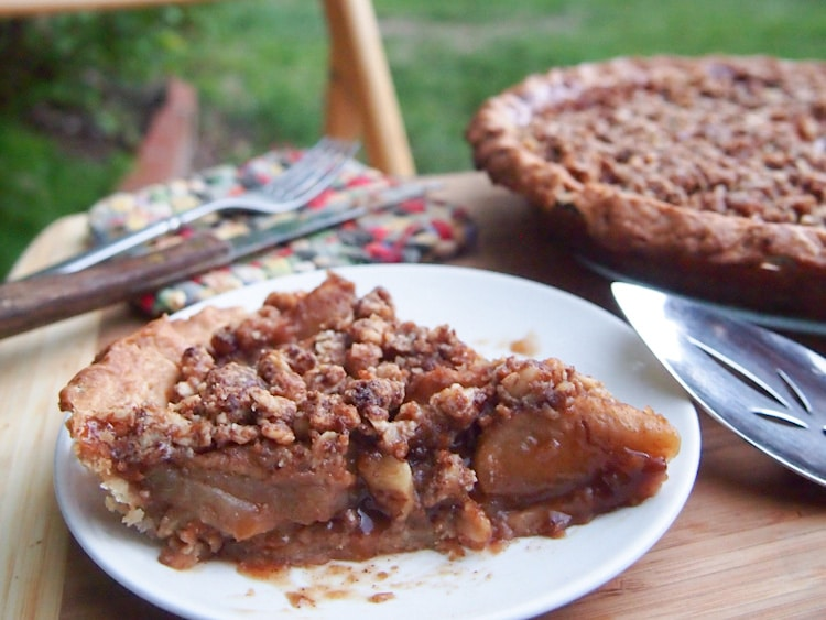 A piece of apple pie with crumble on top with a pie server next to it.