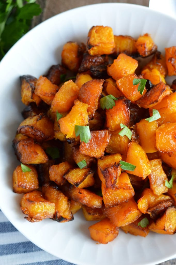 A bowl of caramelized butternut squash topped with fresh parsley.