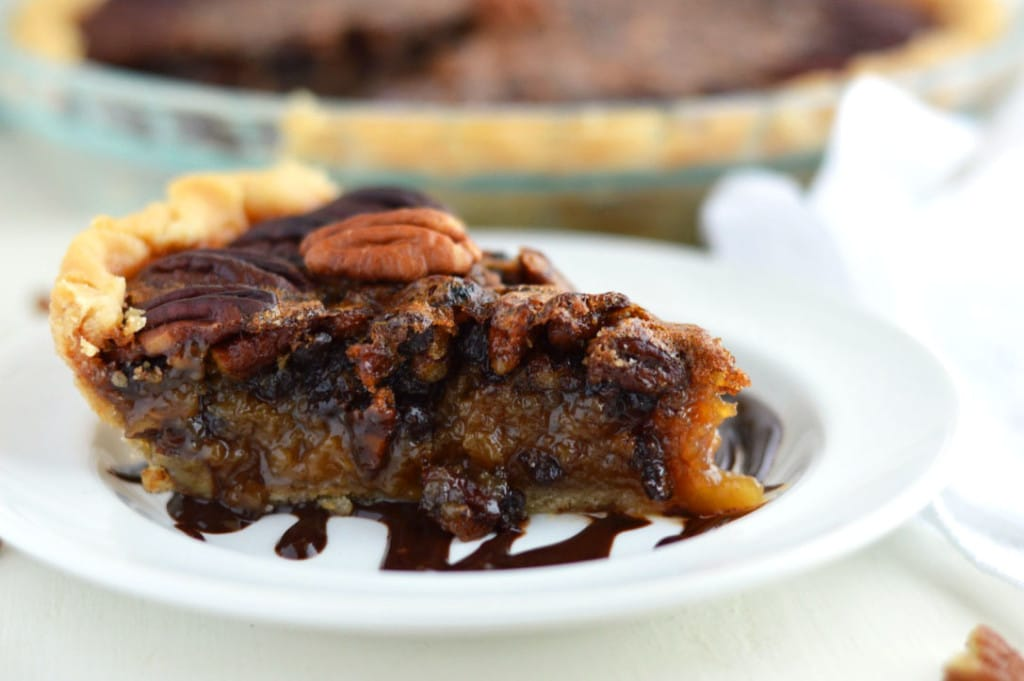 A wedge of chocolate pecan pie on a white plate with a full pie behind it.