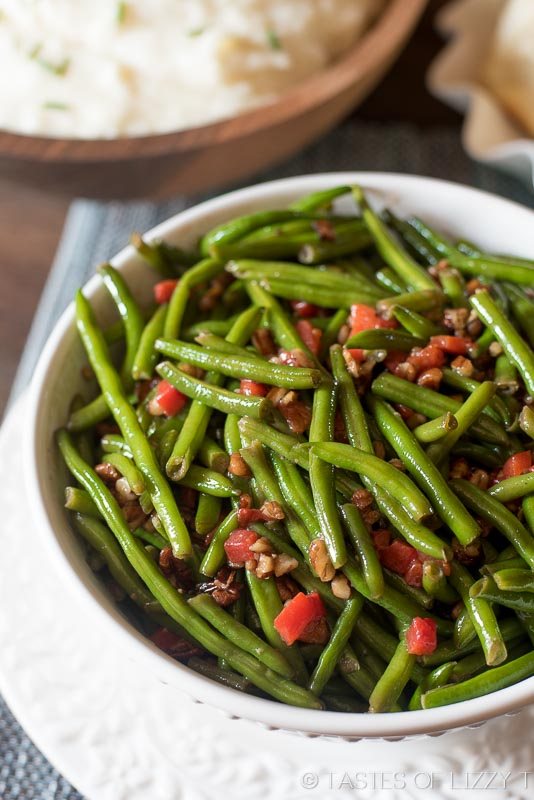 A bowl of green beans topped with chopped pecans.
