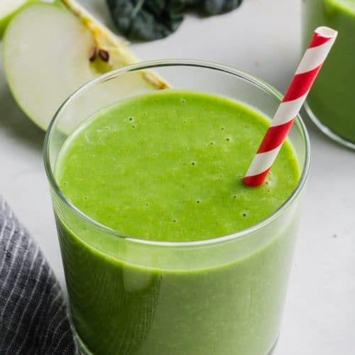 A glass of apple kale smoothie with a red striped straw.