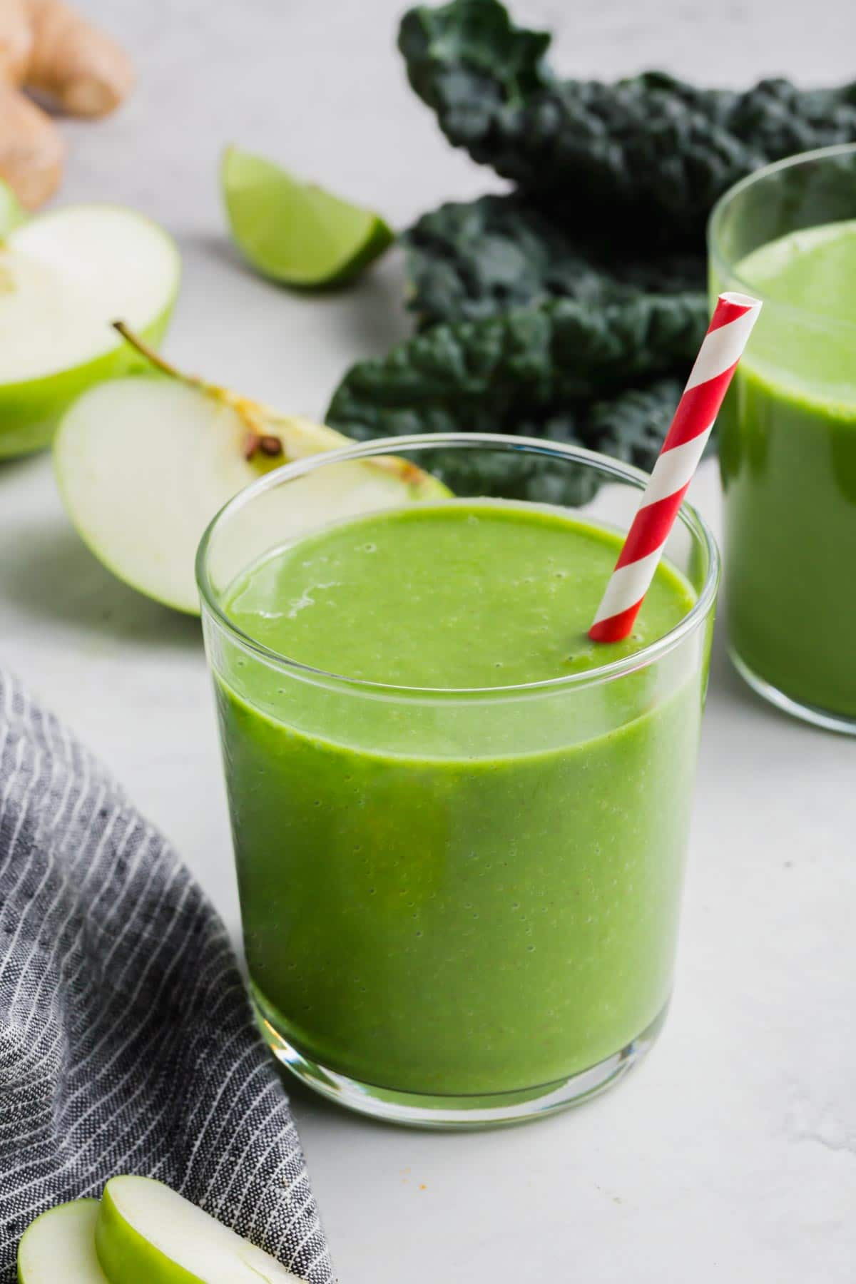 A glass of apple and kale smoothie with a straw.
