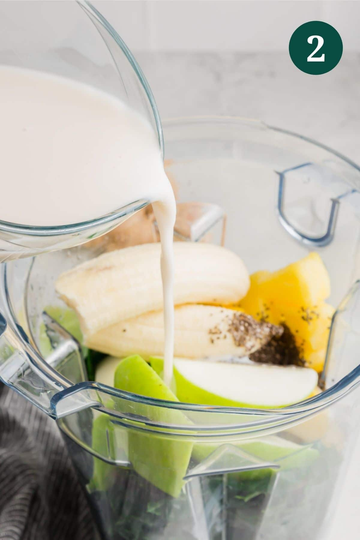 Almond milk being poured into a blend with apple, banana, pineapple and kale.