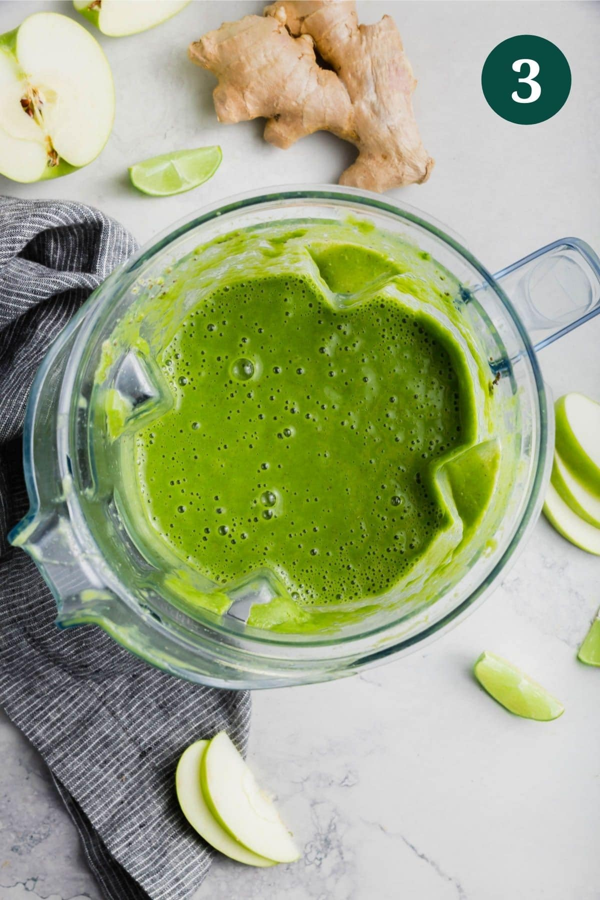 A blender with apple kale green smoothie in it and fresh ginger and apple on the table.