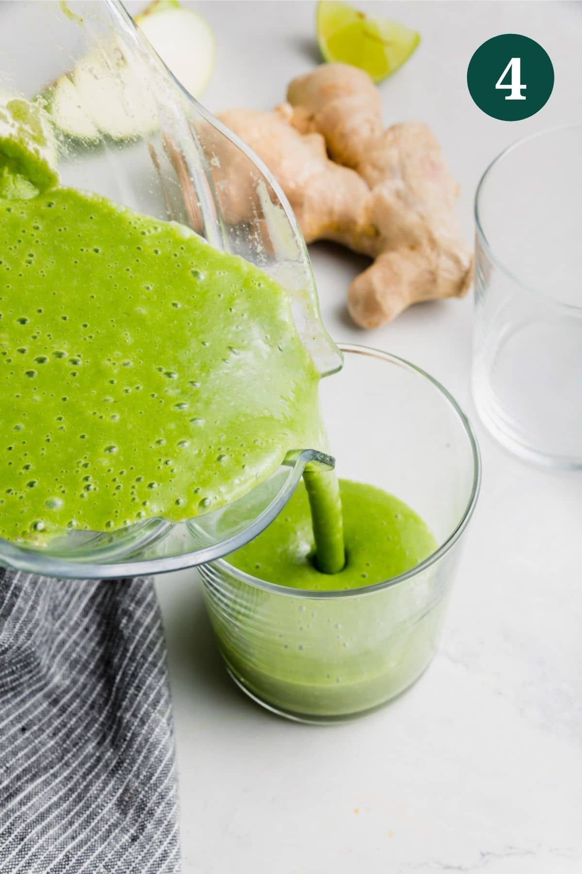 An apple kale green smoothie being poured into a glass.