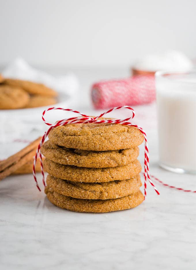 A stack of chewy ginger molasses cookies with a red ribbon and a glass of milk.