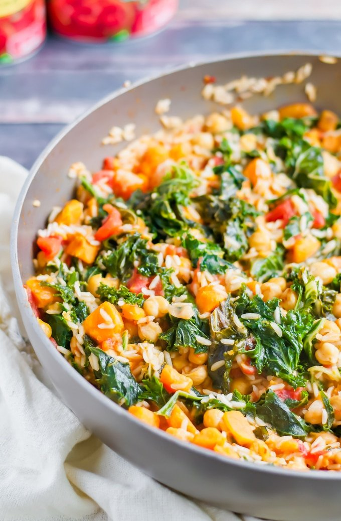A skillet with kale, sweet potato, tomato, and rice.