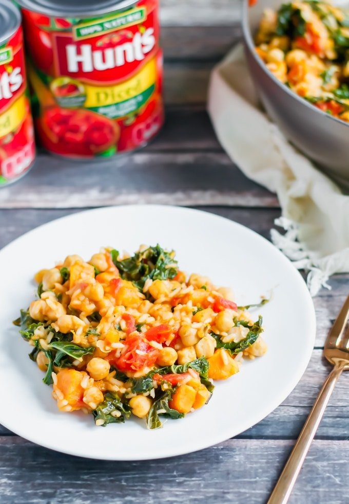 A plate of rice, chickpea, tomato and kale with cans of Hunt's tomatoes in the background.