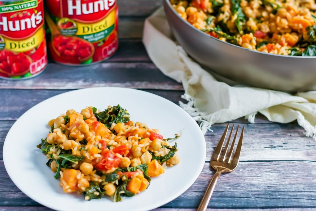 A plate of chickpea kale sweet potato rice skillet with a skillet and cans of diced tomatoes in the background.