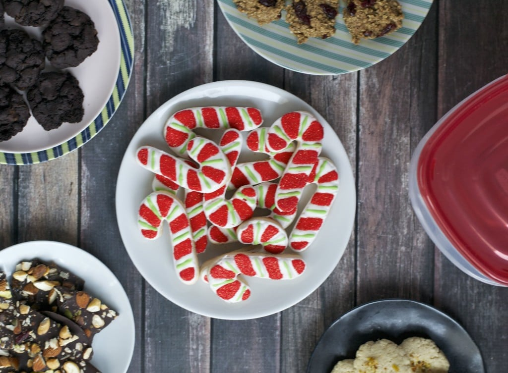 An overhead view of an assortment of cookies on different plates including candy cane cookies.