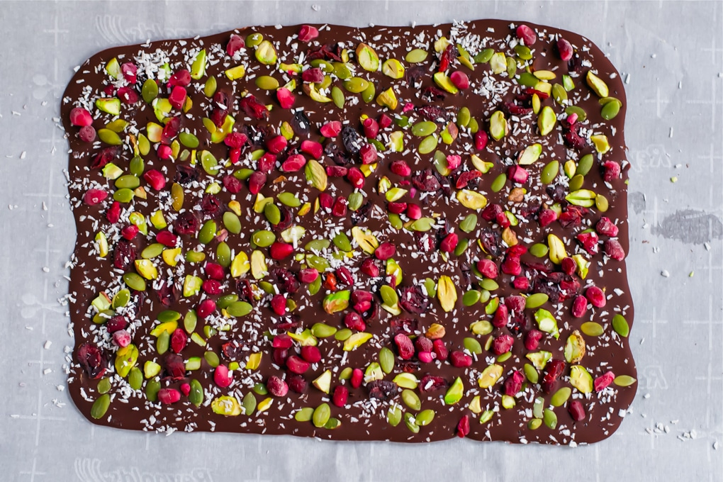 Pistachio pomegranate chocolate bark on a piece of parchment paper before cutting into pieces.