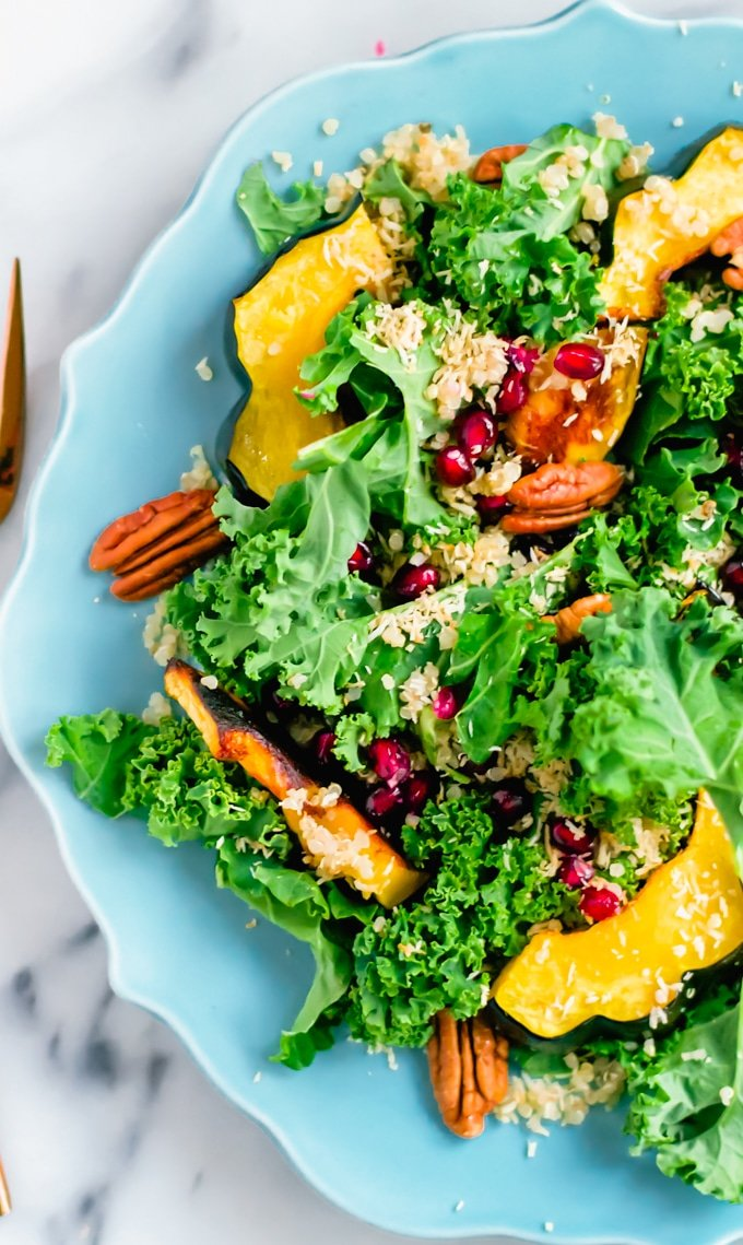 A blue plate with kale salad topped with roasted acorn squash, pecans, toasted coconut, and pomegranate arils.