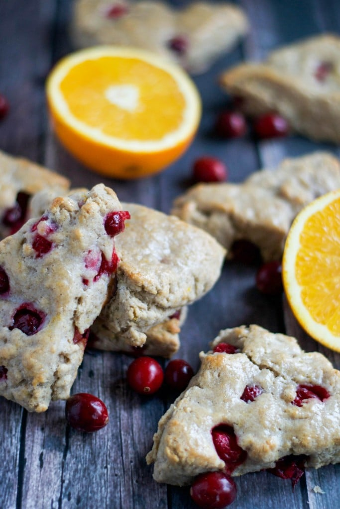 Vegan cranberry orange scones stacked on top of each other with orange halves on a wood table.