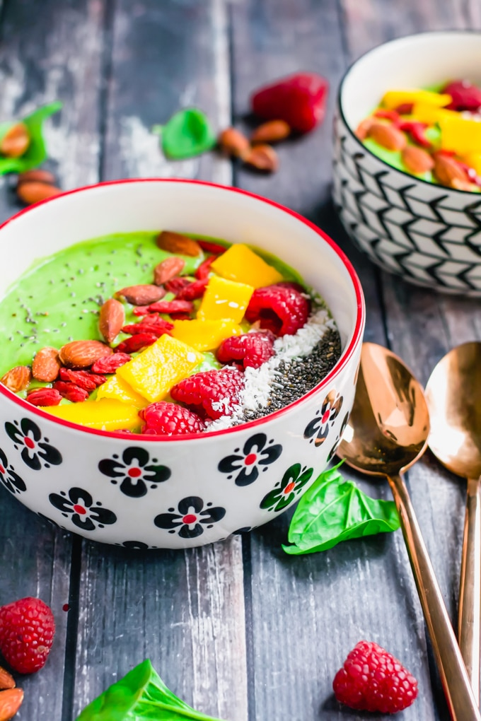 Two bowls of green smoothies topped with raspberries, mango, goji berries, almonds, shredded coconut and chia seeds.