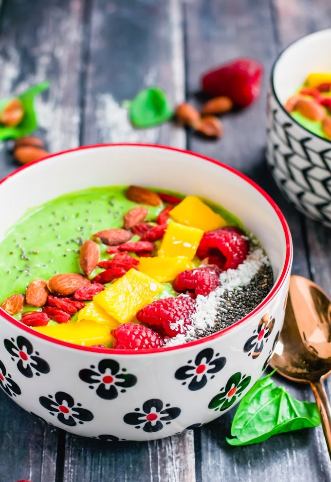 A bowl of green smoothie topped with chia seeds, shredded coconut, raspberries, diced mango, goji berries, and almonds.