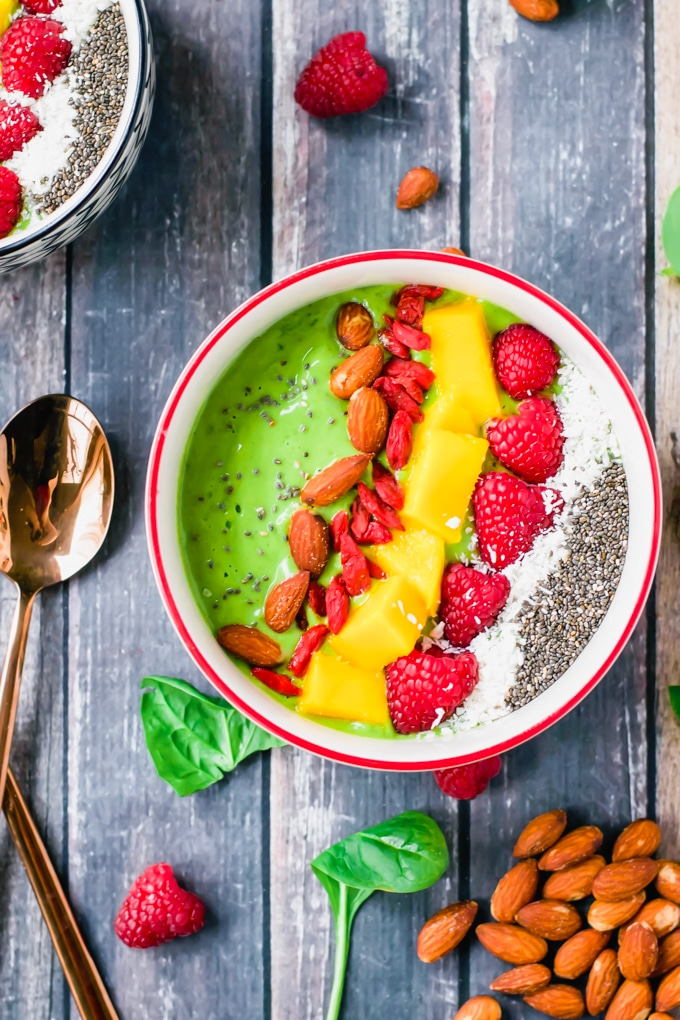 An overhead view of a green smoothie bowl topped with almonds, goji berries, diced mango, raspberries, shredded coconut, and chia seeds.