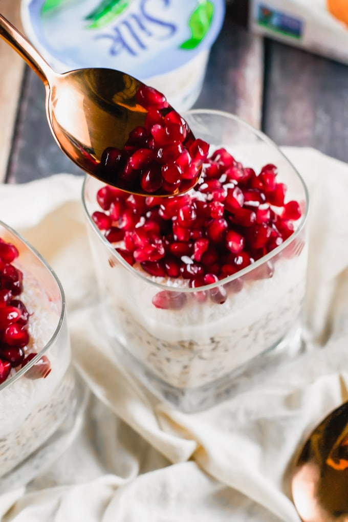 A spoon placing pomegranate arils on top of a glass of overnight oats.