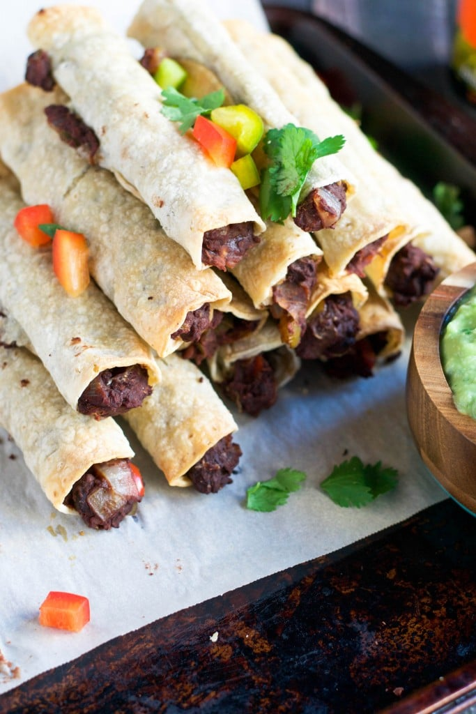 A pyramid of refried bean taquitos on a baking sheet topped with peppers and cilantro.
