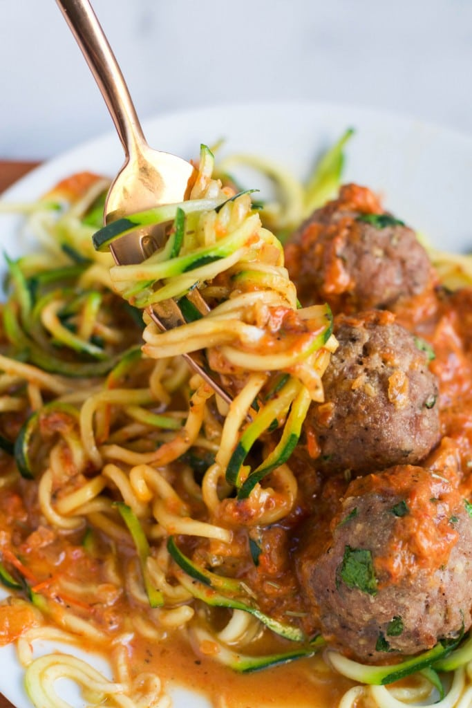 A fork twirling zucchini noodles in a roasted red pepper sauce with some turkey meatballs.