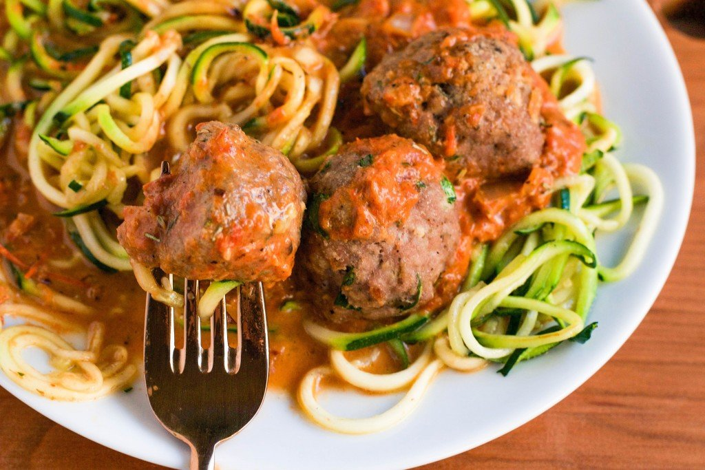 Zoodles with Turkey Meatballs in a Roasted Red Pepper Sauce with a fork sticking into the meatball