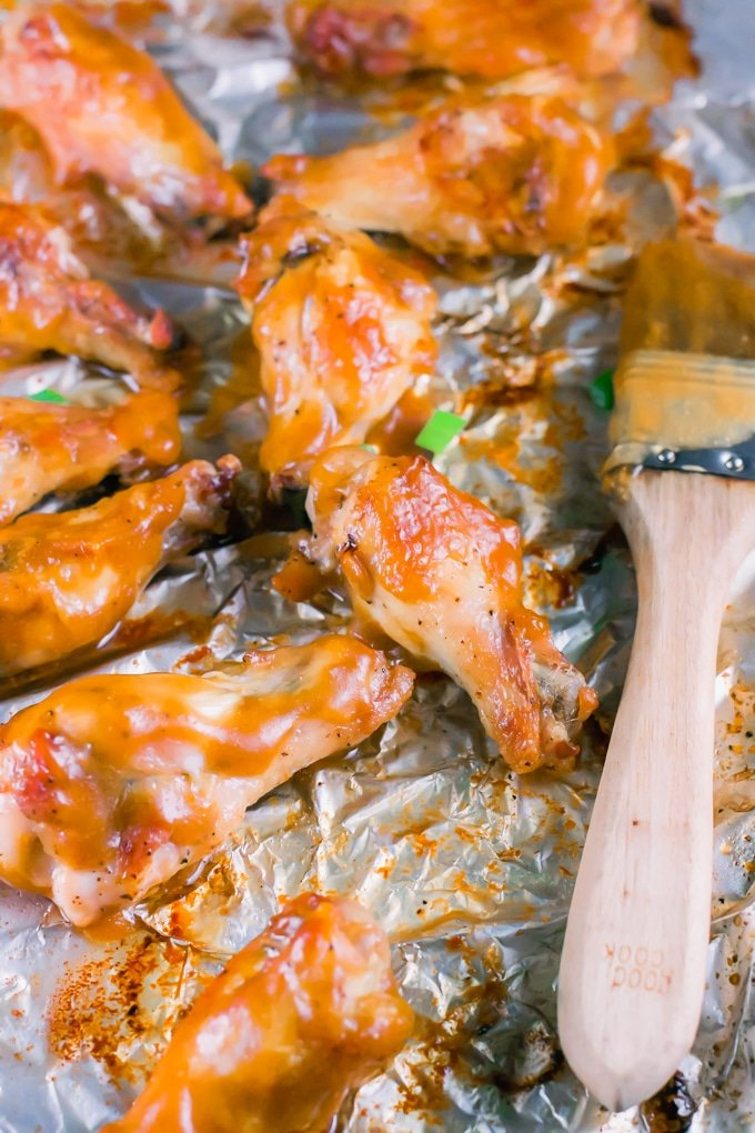 Mango habanero chicken wings on aluminum foil with a pastry brush.
