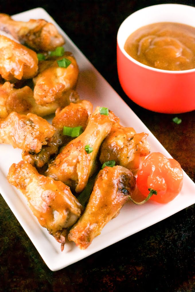 A white rectangular plate of baked mango habanero chicken wings with a bowl of mango habanero sauce in the background.