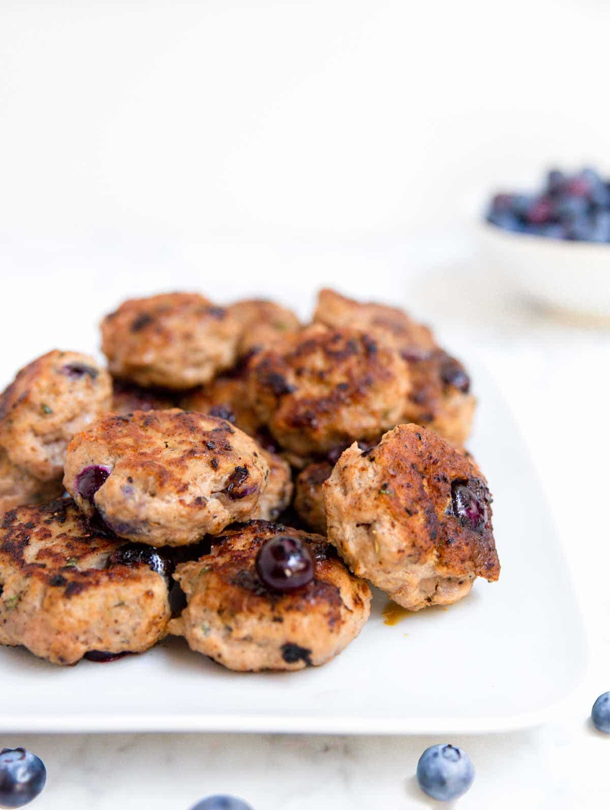 A white platter topped with blueberry turkey breakfast sausage and fresh blueberries.