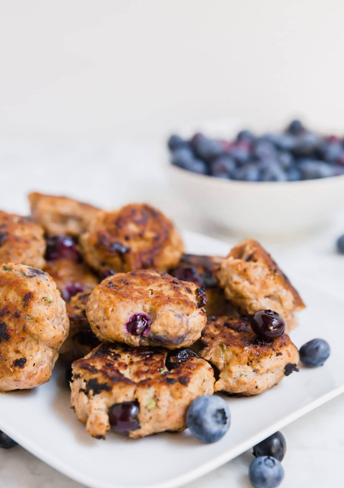 A photo of a white plate with cooked blueberry turkey breakfast sausage with a bowl of fresh blueberries in the background.