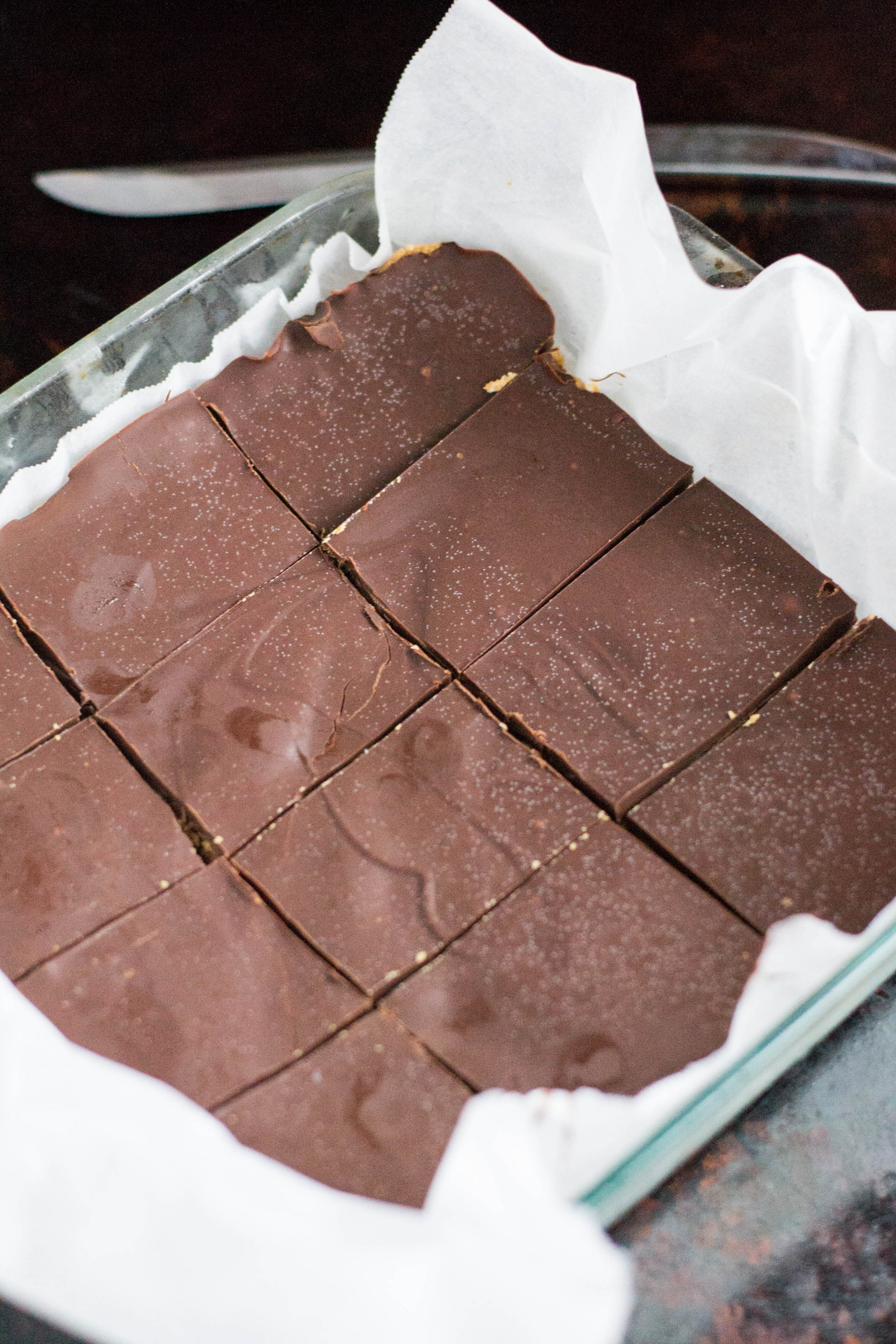 A  baking dish lined with parchment paper containing chocolate peanut butter bars that have been sliced into rectangles.