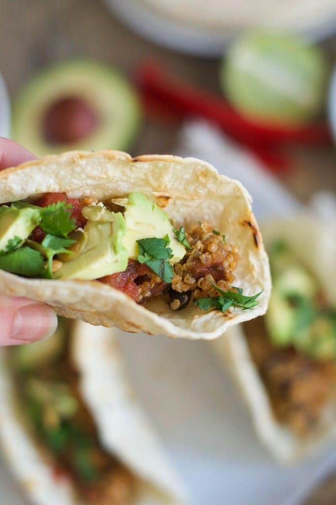 A hand holding a vegan quinoa taco with salsa, avocado and cilantro.