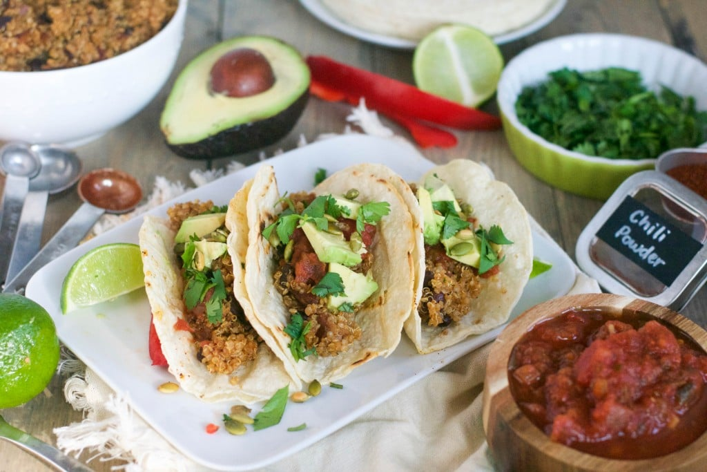 A platter with vegan quinoa tacos with avocado, cilantro and salsa on it with bowls of cilantro, quinoa, and salsa on the side.
