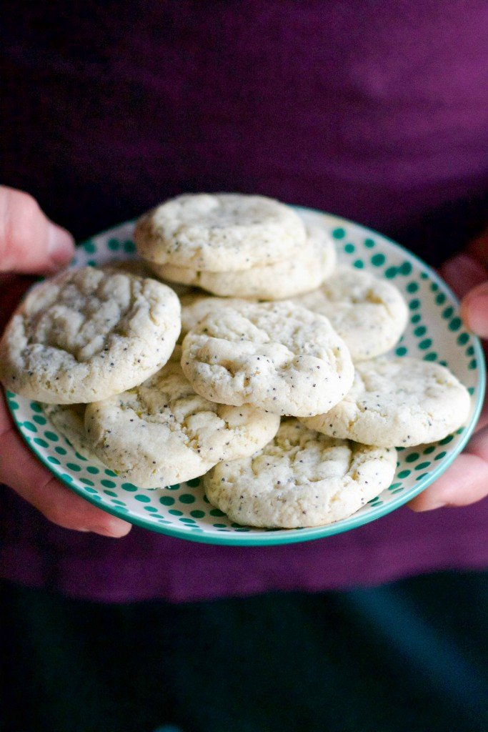 A person holding a small plate of lime poppyseed cookies.