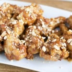 White plate of baked peanut butter chicken wings topped with chopped roasted peanuts.