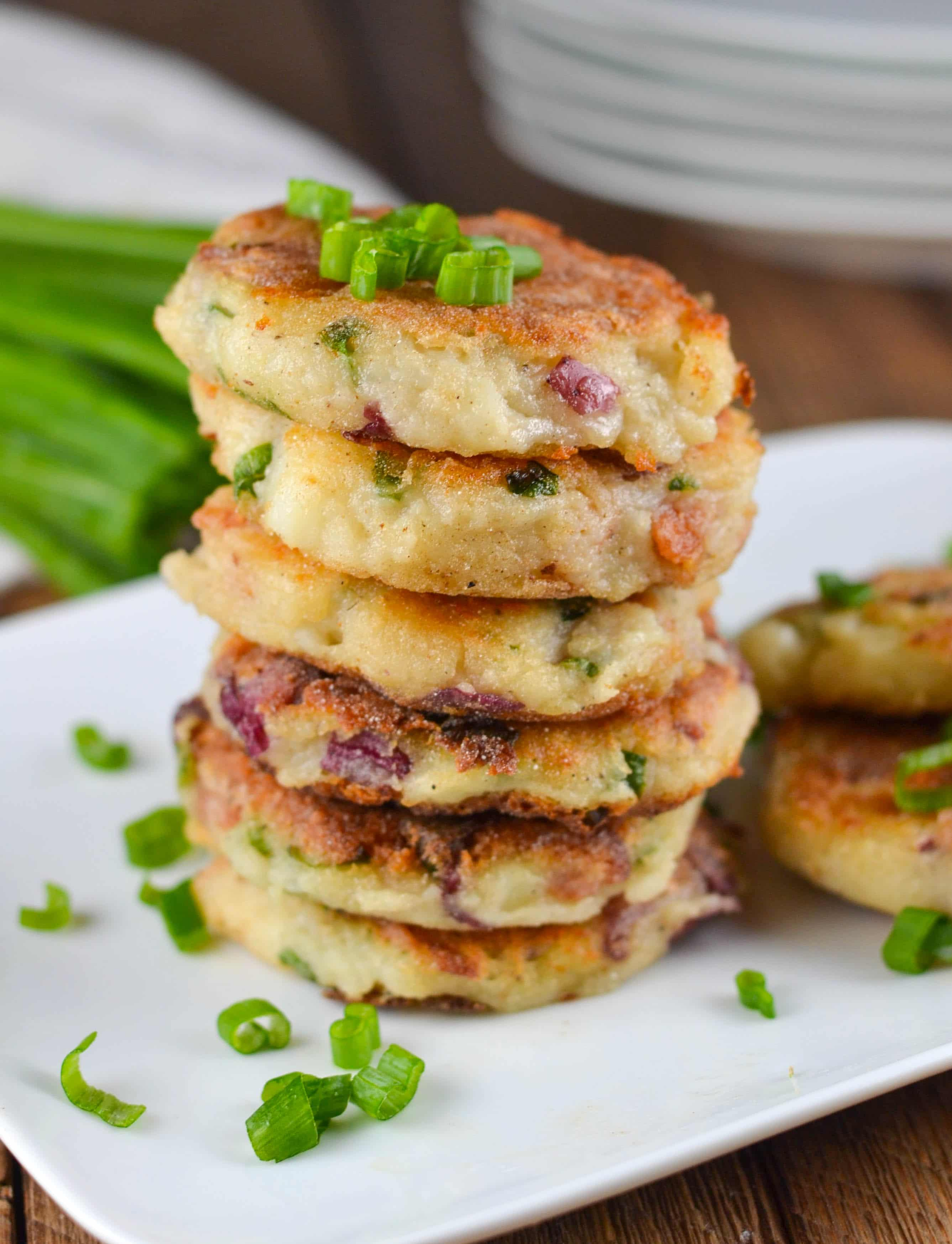 A stack of mashed potato cakes topped with green onions and bacon.