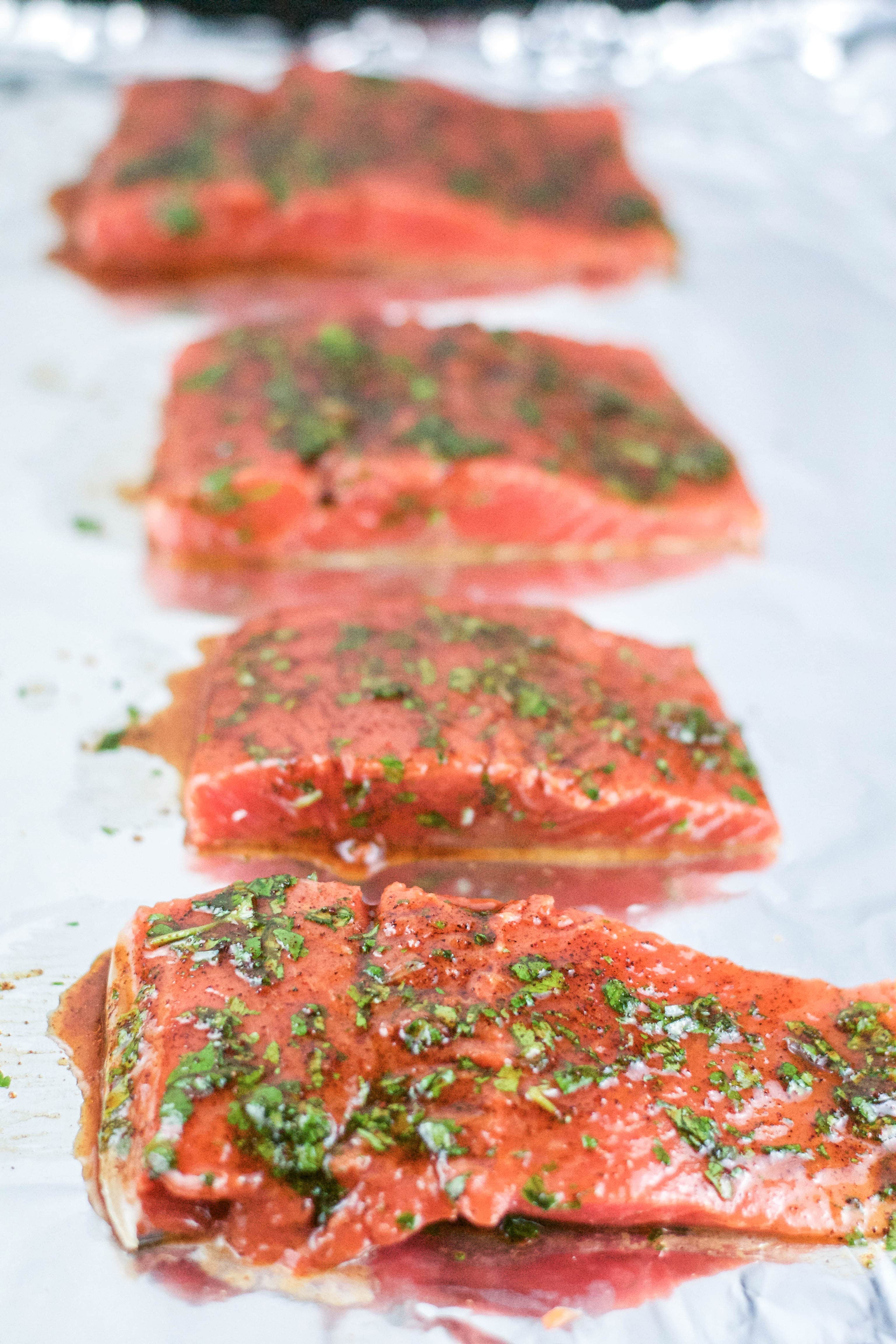 Raw salmon portions with cilantro and honey glaze on a baking sheet lined with aluminum foil.