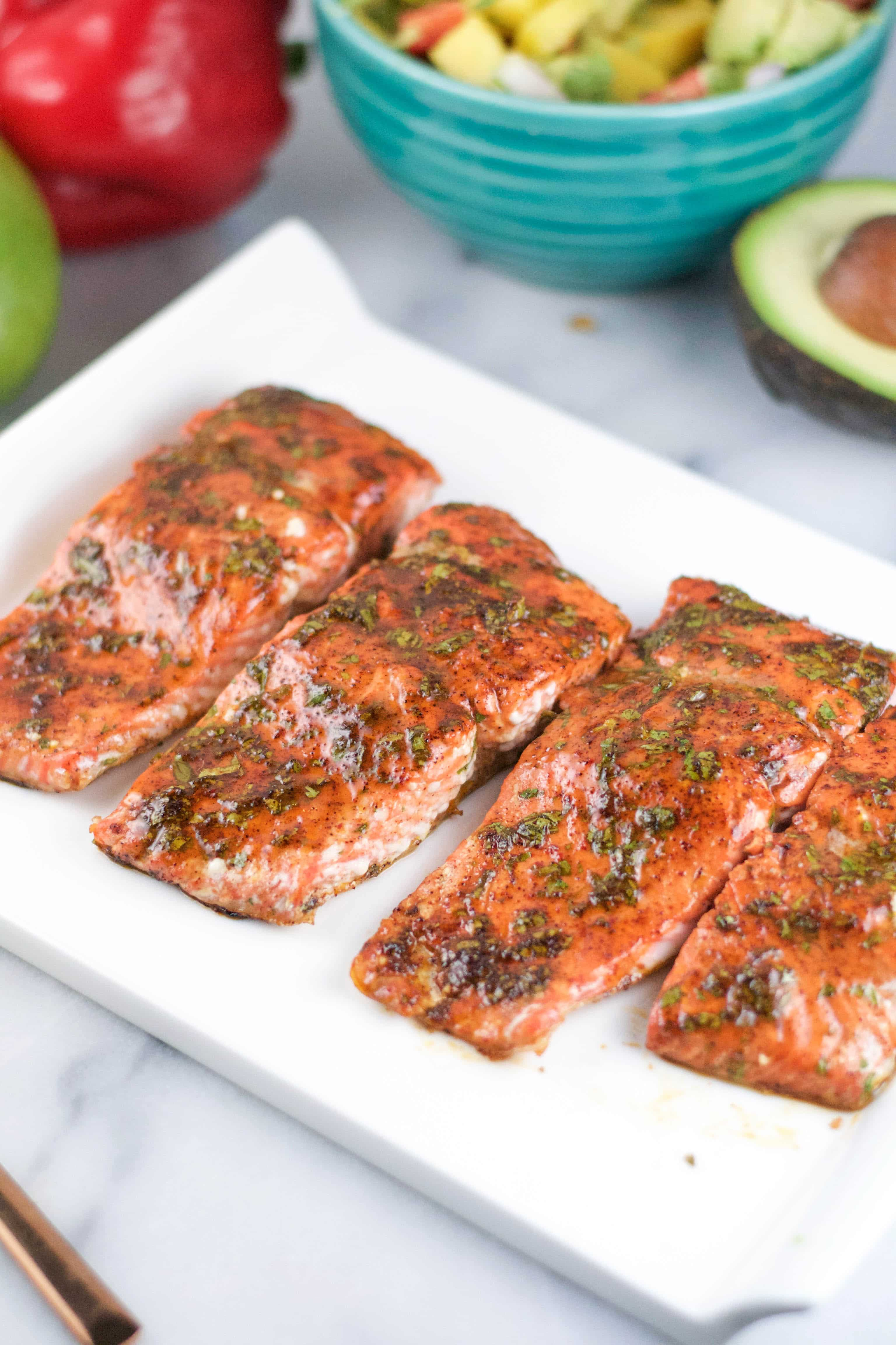 A platter of salmon portions with cilantro honey glaze on top.