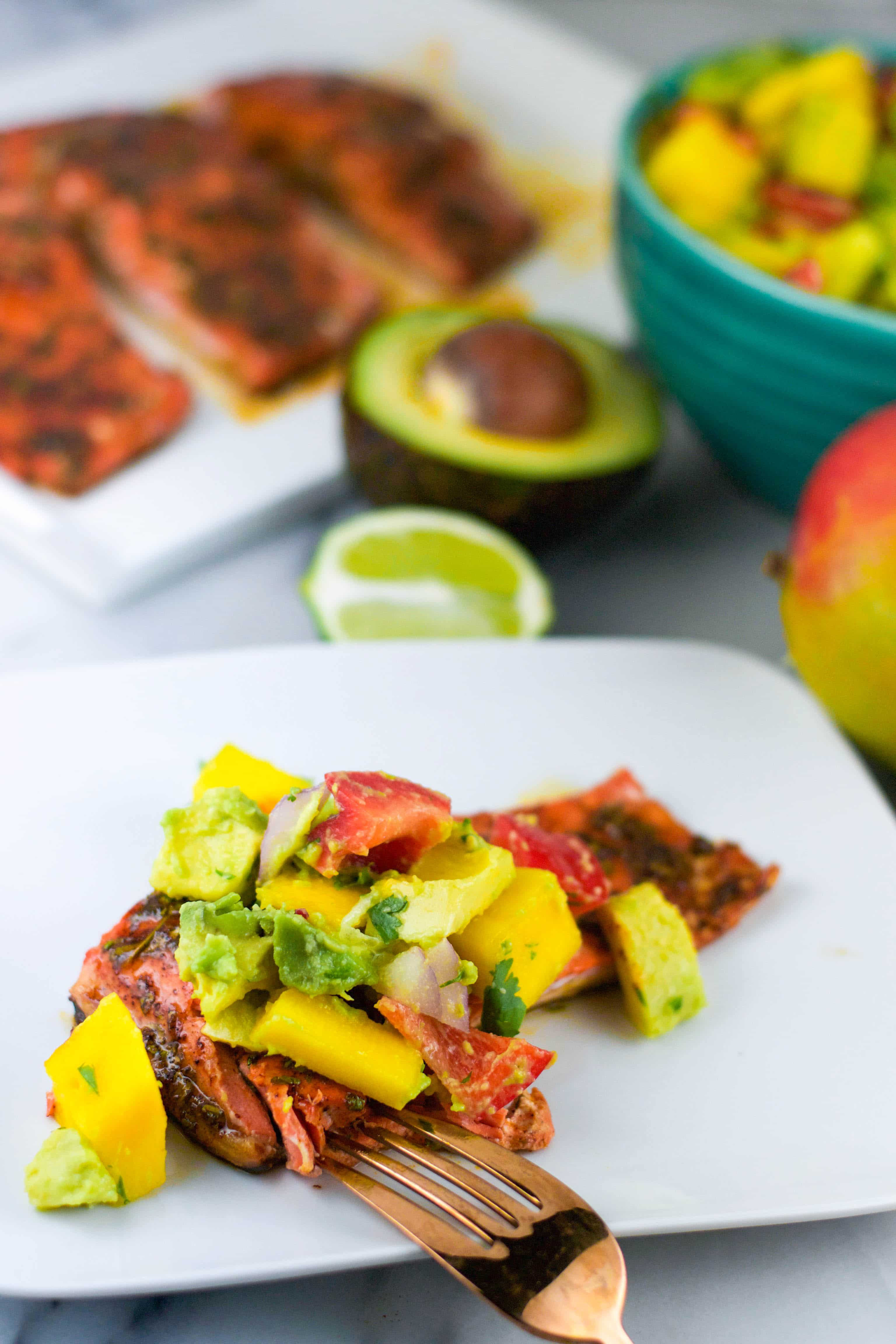 a plate of salmon with avocado mango salsa on top with a fork next to it.