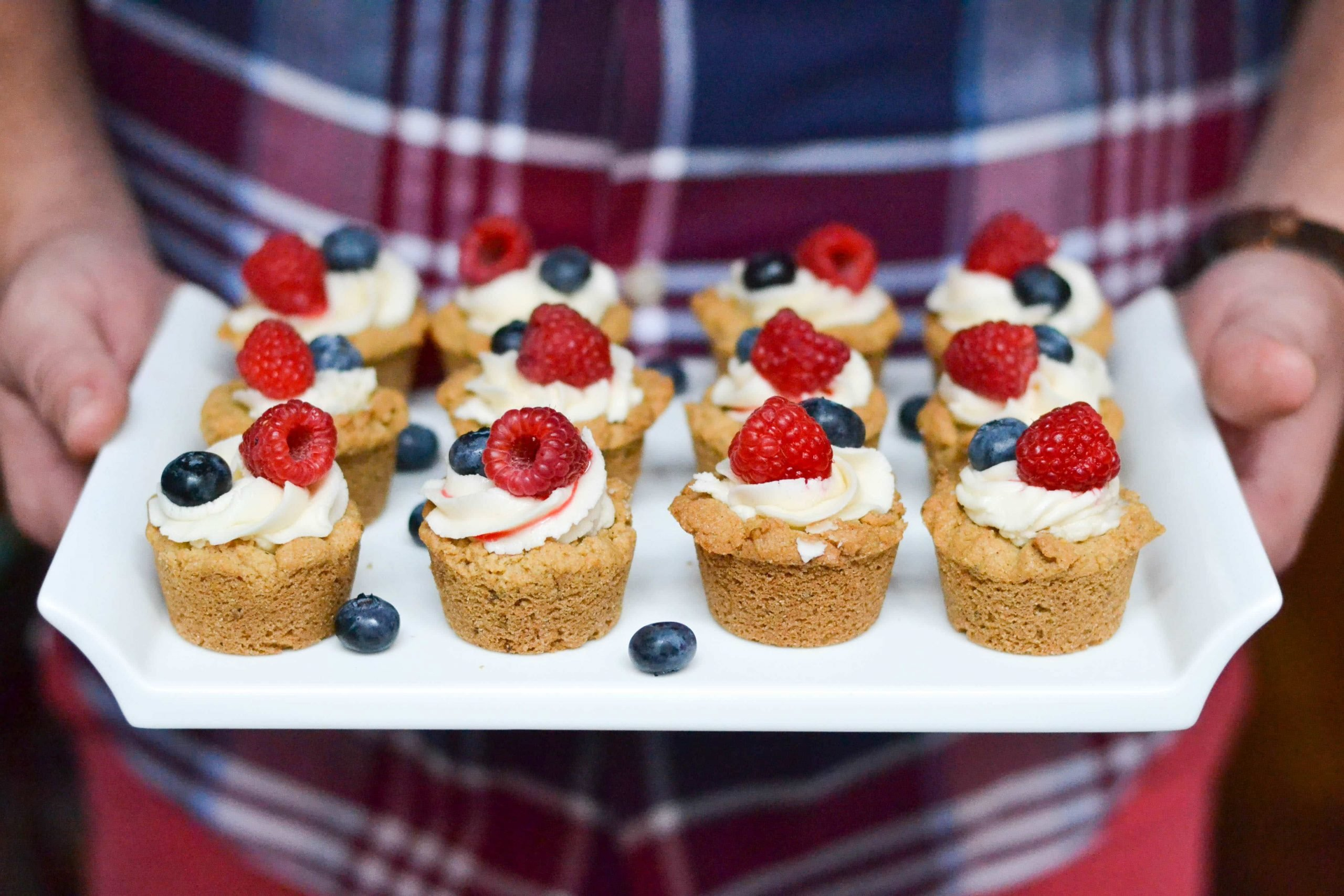 A person holding a platter of mini cookie cups topped with buttercream, raspberries and blueberries.