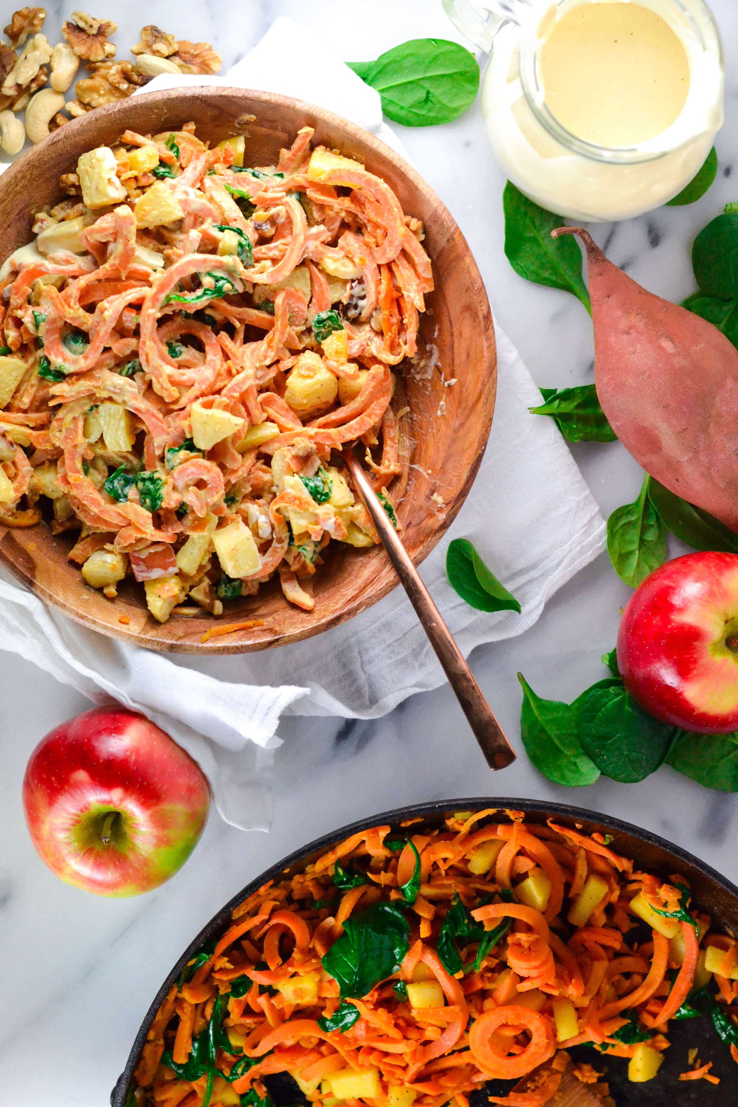 A wood bowl with Sweet Potato Noodles and apples  in a Creamy Cashew Sauce with apples on the table.