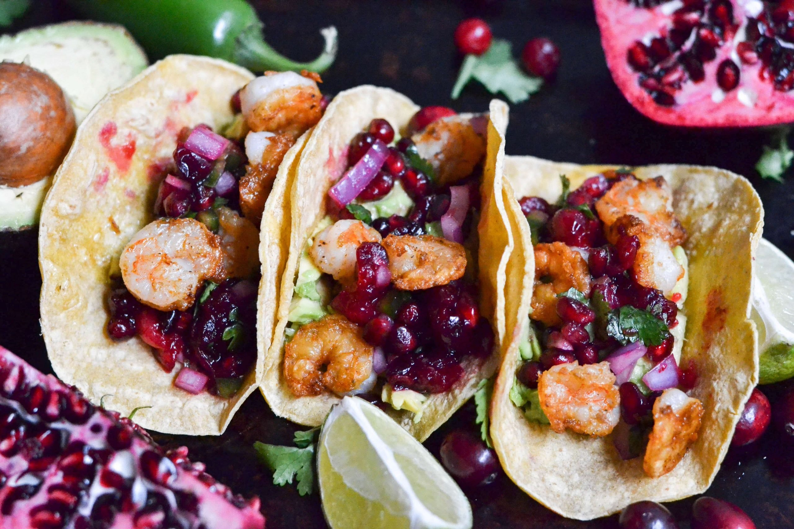 Three cranberry pomegranate shrimp tacos with lime wedges on a baking sheet.